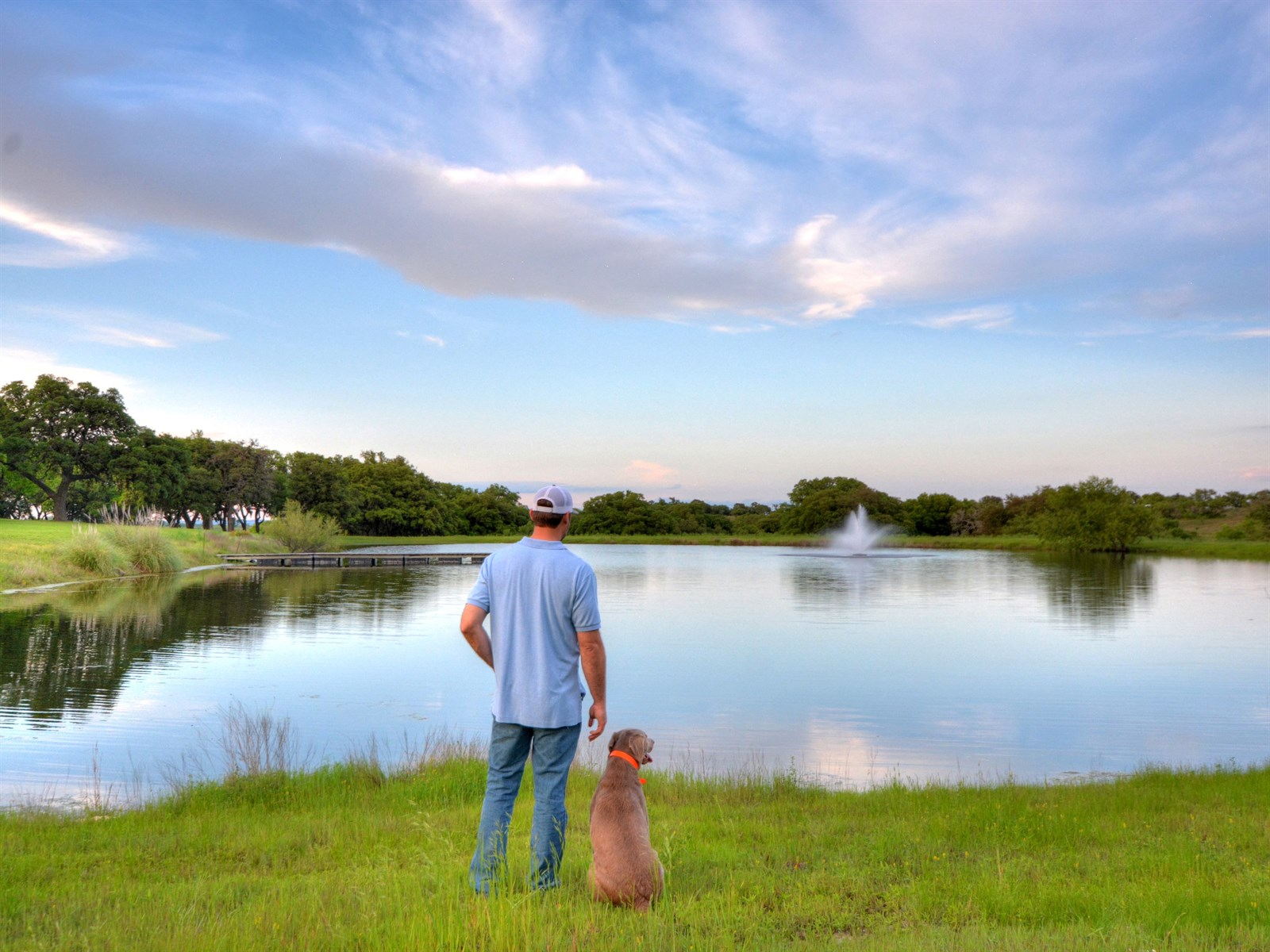 man with dog at pond