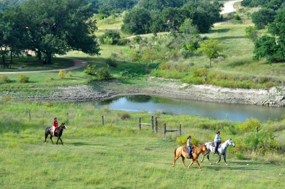 people by river on horseback